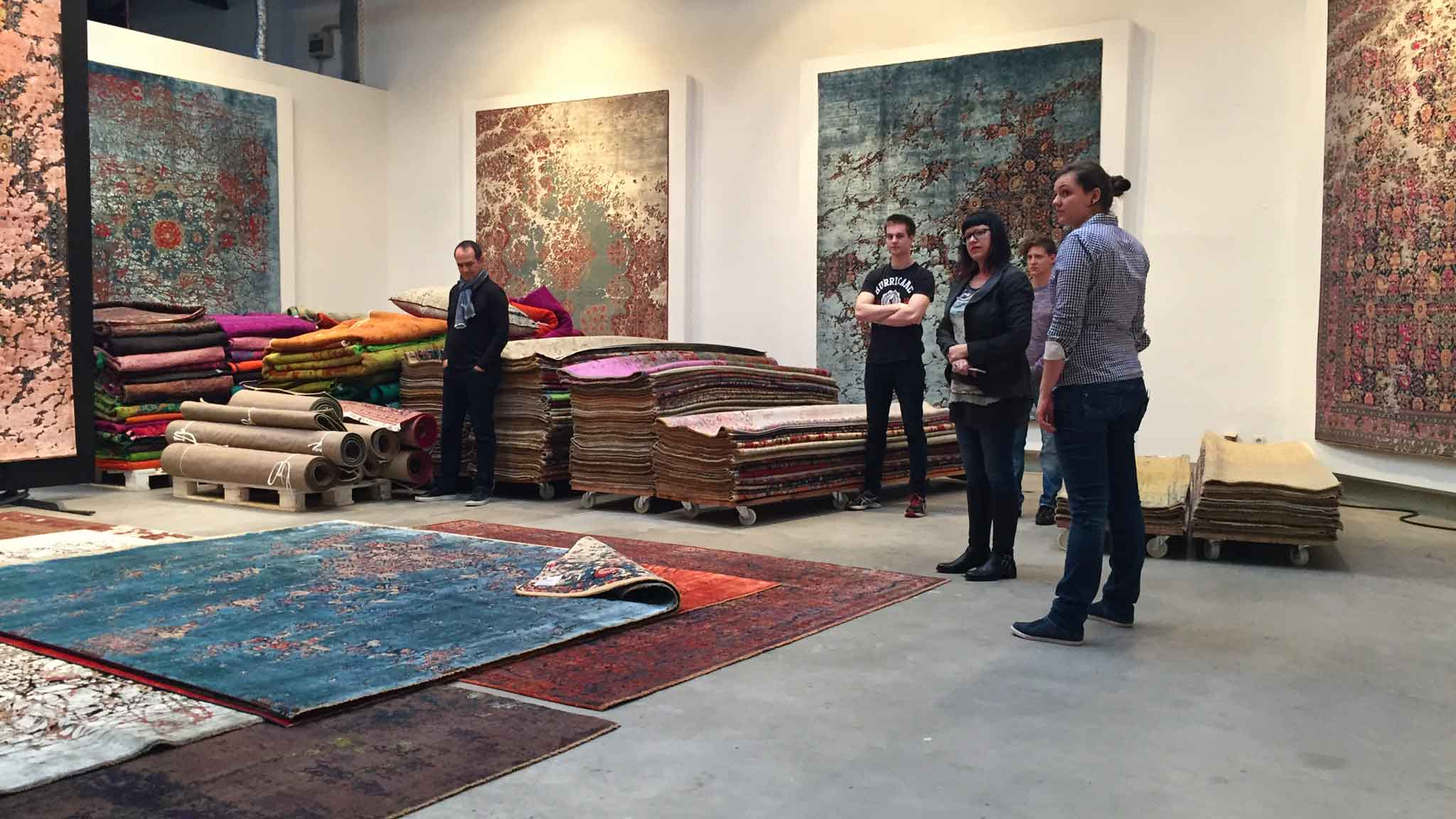 Jan Kath Showroom partners Jacques Miodownik (left), Jenni Finlay (third from left), and showroom staff listen as Jan Kath (off camera) explains elements of new carpets. | Image from The Ruggist.