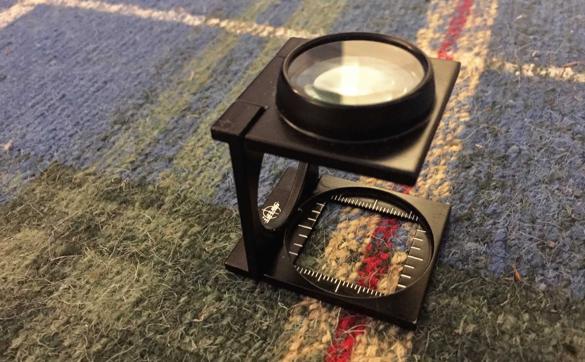 A linen tester is utilized to more easily count and verify the number of knots per square inch in any carpet. The Ruggist's trusty and now twenty-one (21) year old linen tester is shown here on a custom Nova Scotia Tartan carpet made by New Moon for The Ruggist in 2009. | Image courtesy of The Ruggist.