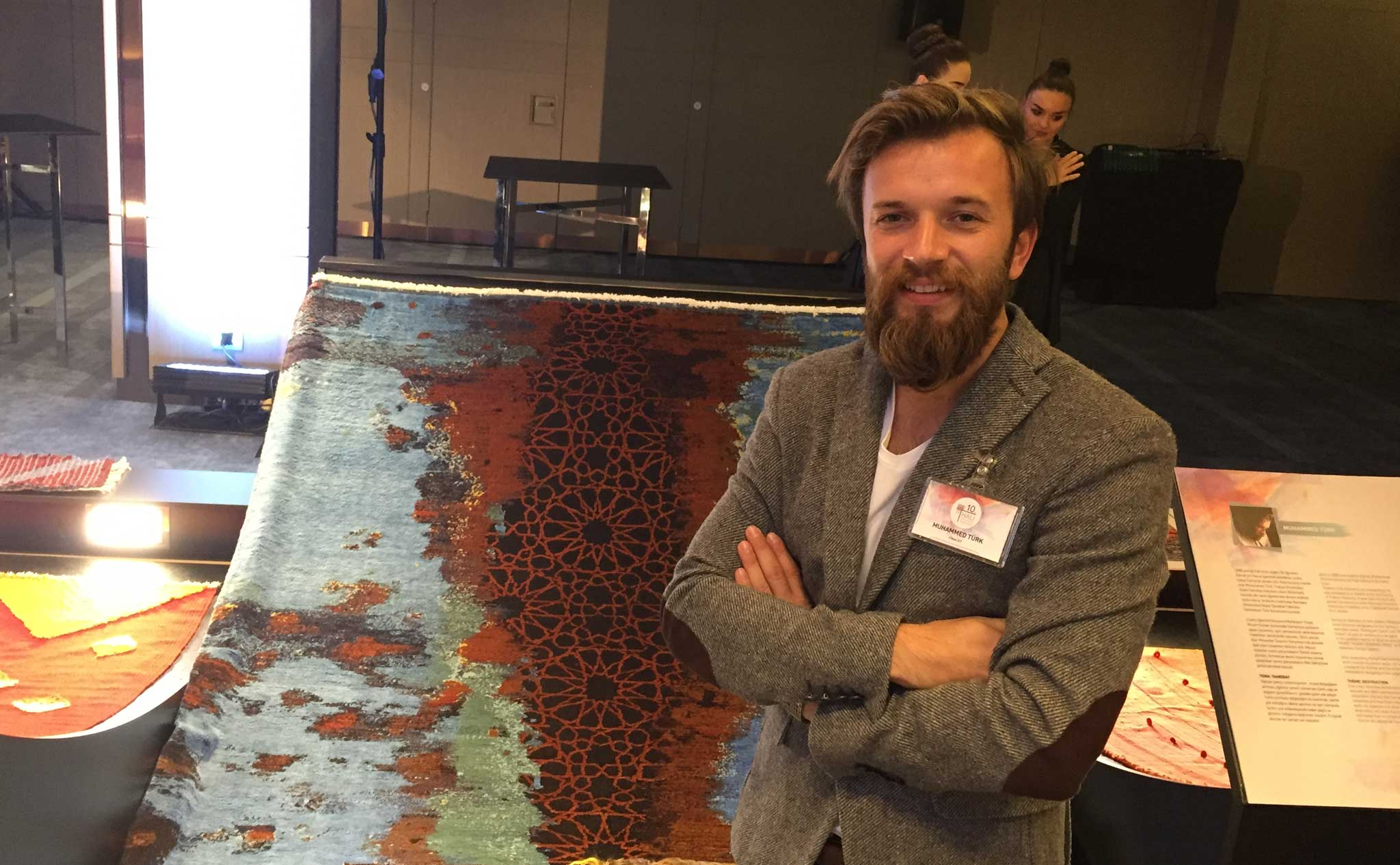 Muhammed Türk is shown with his carpet 'Destruction' which won the tenth (10th) annual Turkish Carpet Design Awards presented by IHIB. | Image courtesy of The Ruggist.