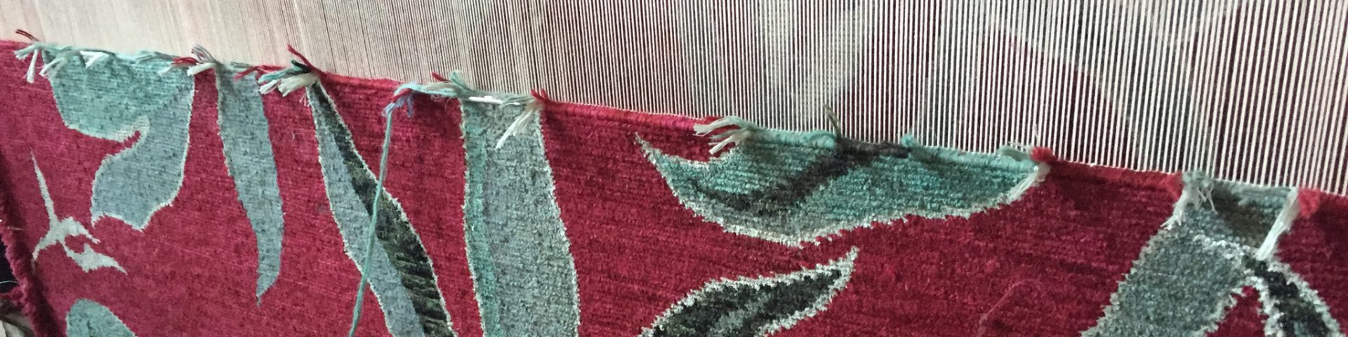 'Camara' in colour 'Oxblood' by New Moon shown on loom in Nepal. | Image courtesy of The Ruggist.