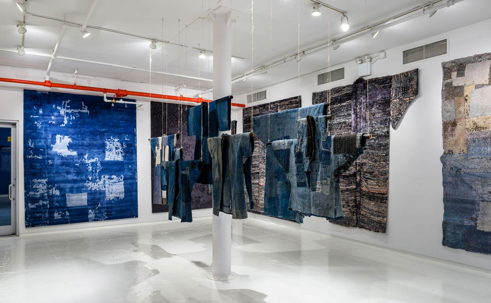 Traditional Boro textile garments (on loan to Jan Kath from a private collection) displayed in juxtaposition to the firm's contemporary carpet collection by the same name. | Image courtesy of Jan Kath.