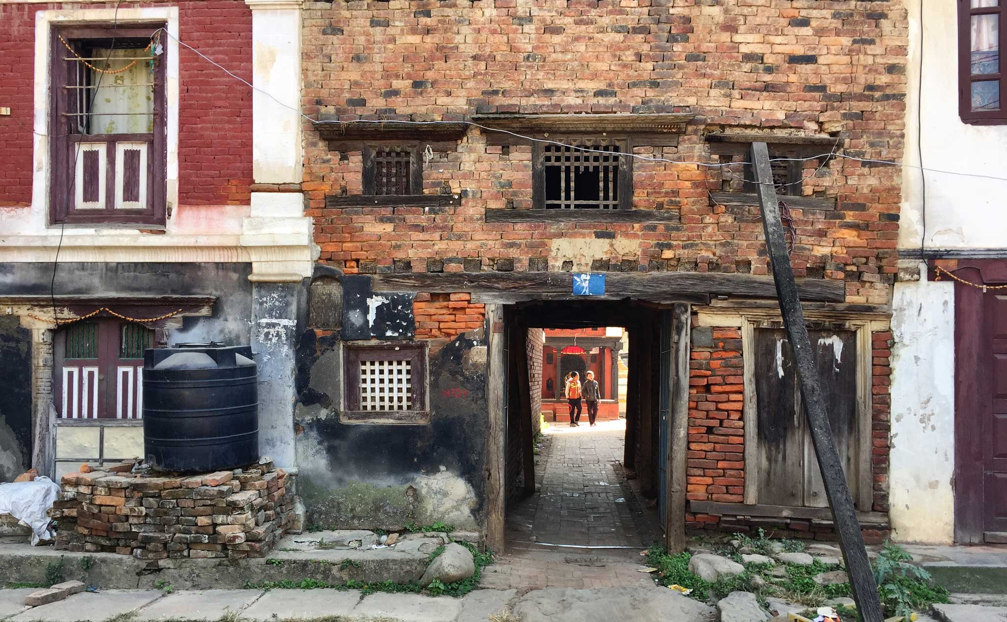 Two young Nepalis seen through a portal in an earthquake damaged building in Patan. | Image by The Ruggist.