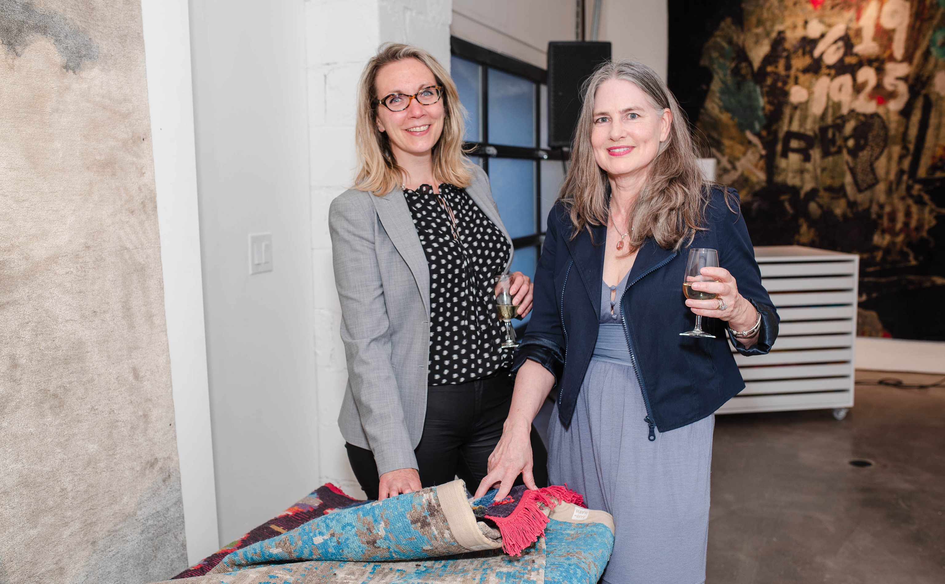 Unidentified women shown browsing carpets and enjoying libations during the opening of Finlay and Kath's new Jan Kath Toronto showroom on Thursday, 10 May 2018. | Image courtesy of Finlay and Kath.