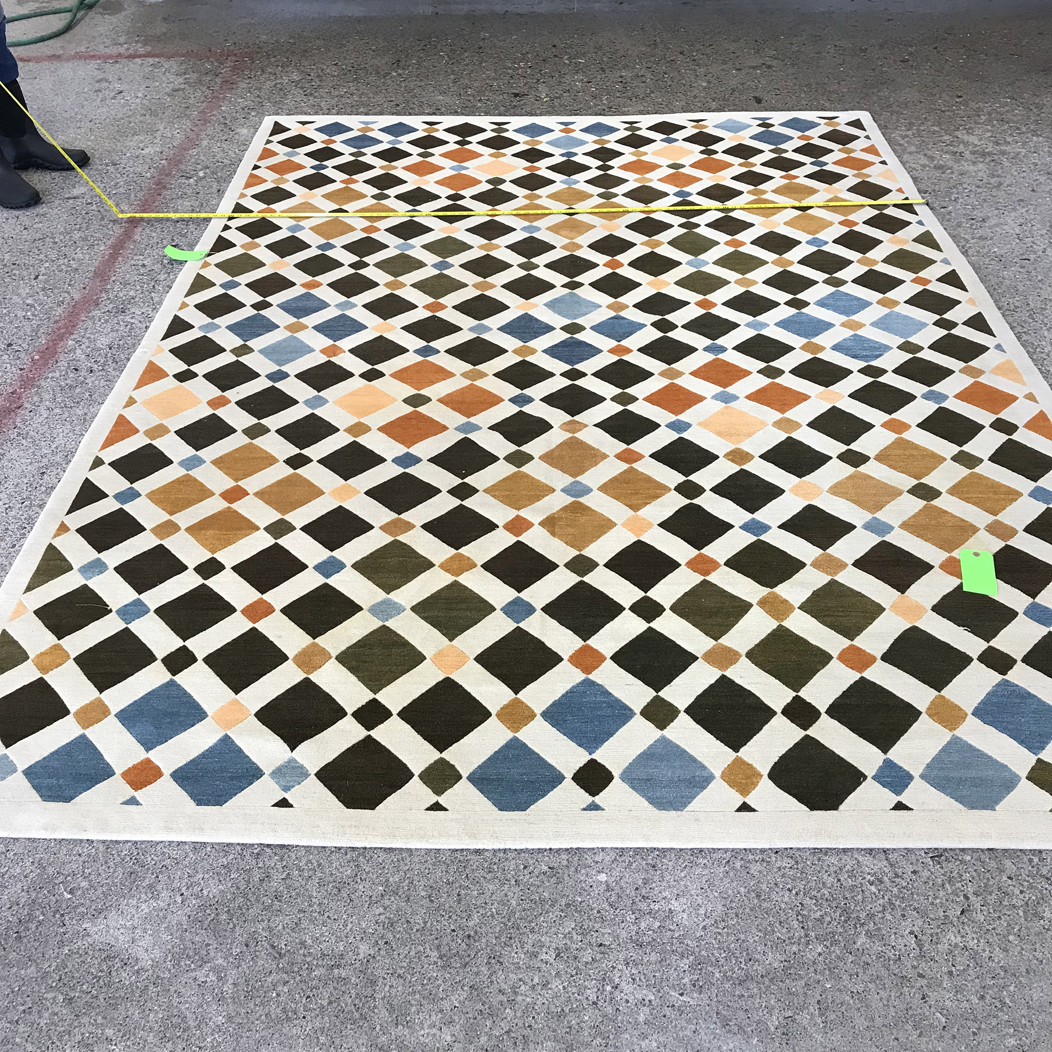A trusted cleaner will thoroughly assess a rug or carpet prior to cleaning. Here you see a technician measuring the carpet to confirm dimensions and provide documentary information should problems arise. | Image courtesy of Weaver & Loom.