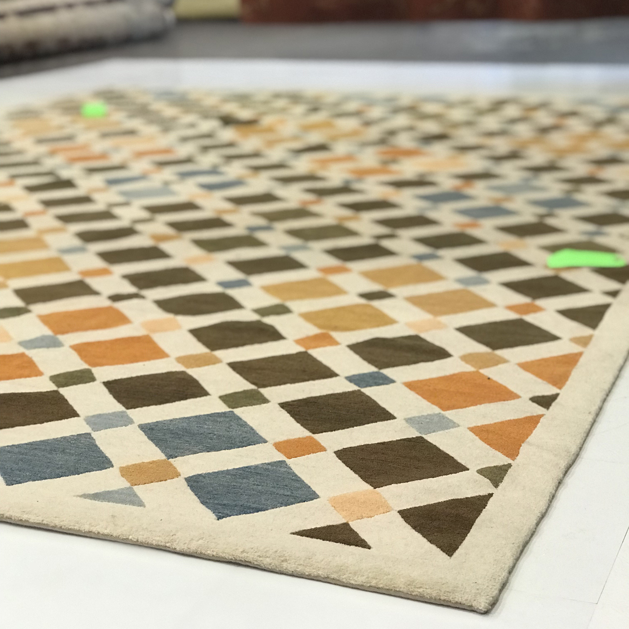 A trusted cleaner will thoroughly assess a rug or carpet prior to cleaning. Here you see 'Tile' laid flat for examination. The green tags were attached prior to shipment in order to show areas requiring extra attention. | Image courtesy of Weaver & Loom.