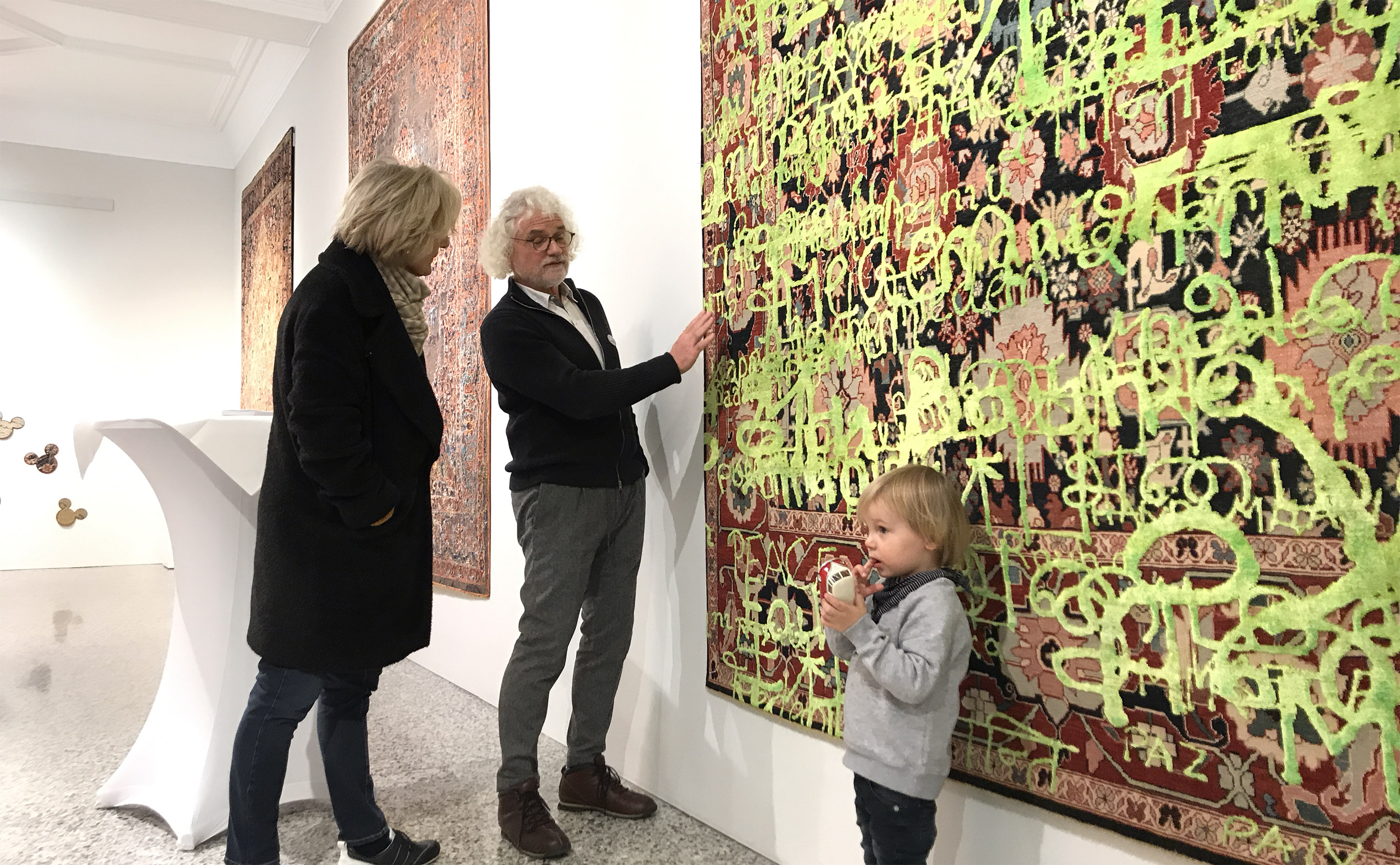 Frank Rüter (centre) of Nyhues - Contemporary Art Rugs shown explaining a carpet from Jan Kath to a prospective client during the 'Make Rugs Not War' vernissage at Jan Kath Köln on 15 January 2019. | Photograph by The Ruggist.