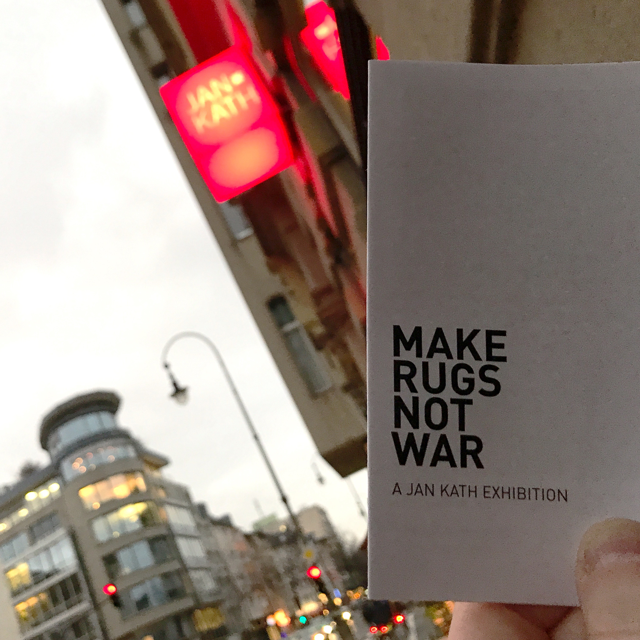 Opening night of the 'Make Rugs Not War' exhibition at Jan Kath Köln by Nyhues -Contemporary Art Rugs. The cover of the pamphlet distributed during the vernissage is shown. | Photograph by The Ruggist.